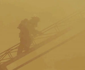 in smoky atmosphere a fireman on a leather going to the rooftop