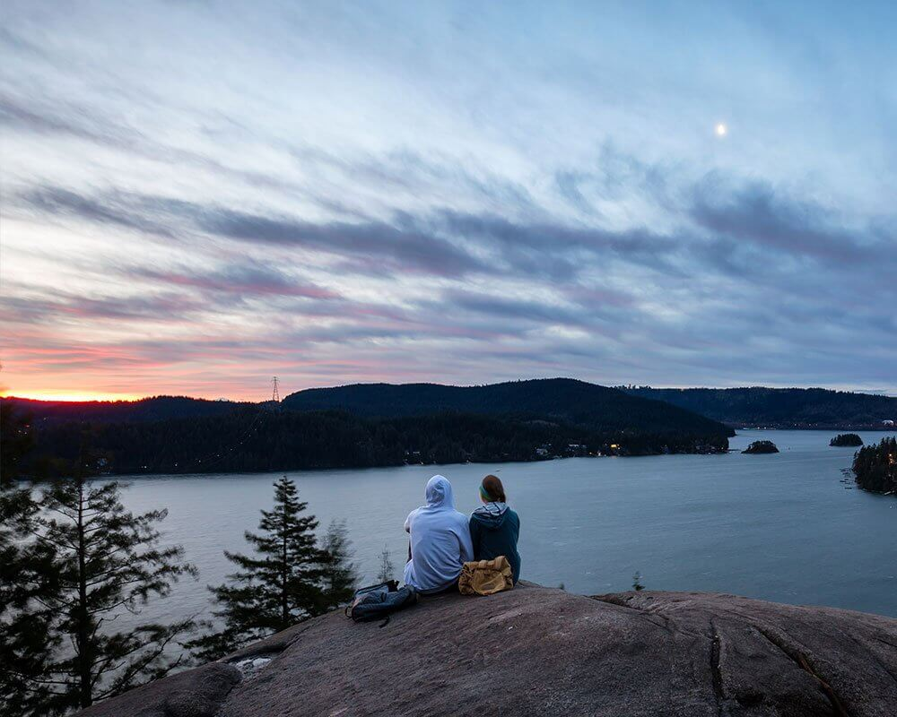couple hikers seating down peacefully looking at a sunset over a lake